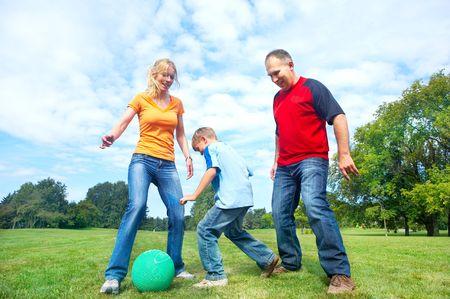 ni�os jugando en el parque: Happy family. Padre, madre e hijos a jugar al f�tbol en el parque