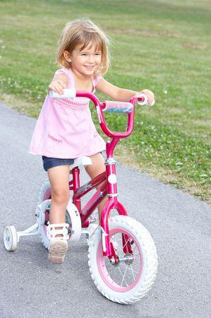 free riding: sorridente ragazzina in bicicletta nel parco