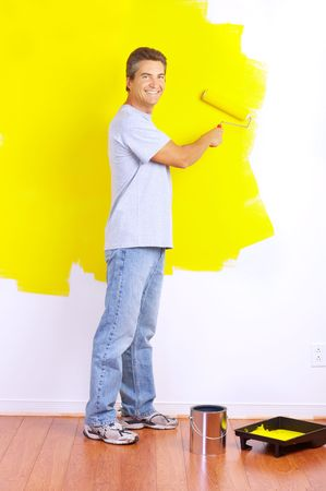 paints: smiling handsome man near the painted  interior wall of home.