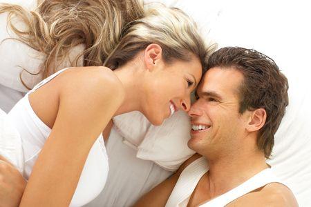 enamorados en la cama: Pareja joven feliz en una cama