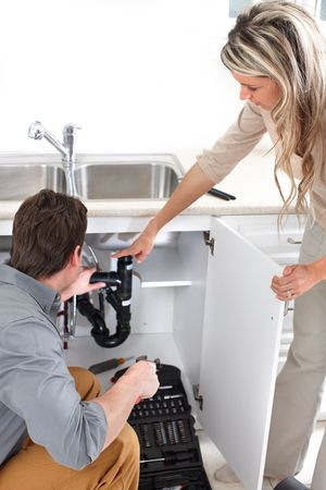 sink drain: Young plumber fixing a sink