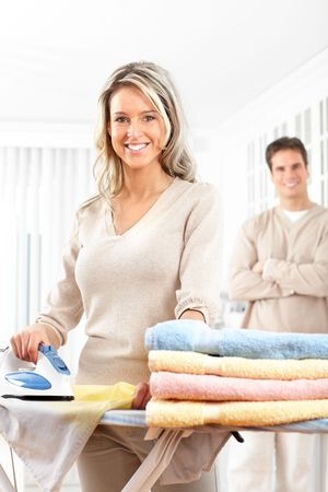 laundry room: Happy young beautiful woman ironing clothes. Housework