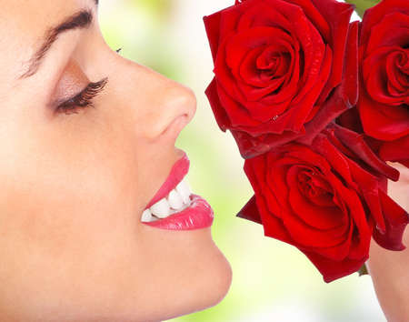 Smiling woman smelling the flowers. Close up