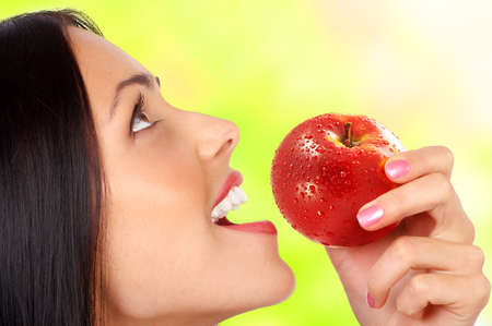 Beautiful young woman eating the red apple. Over green background 