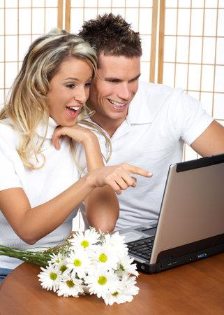 Pares j�venes del amor con la computadora port�til. Fondo blanco excesivo Foto de archivo