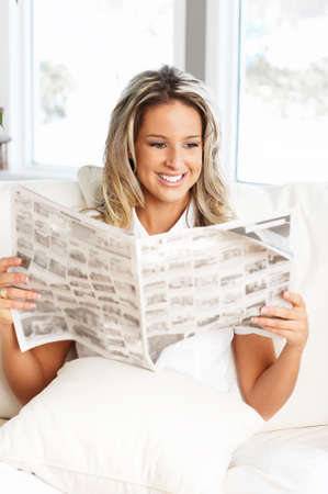 Young  woman reading a newspaper  in the comfortable apartment  photo