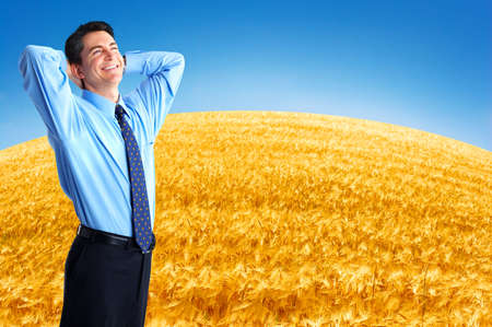 agronomist: Happy successful  businessman in the field under blue sky