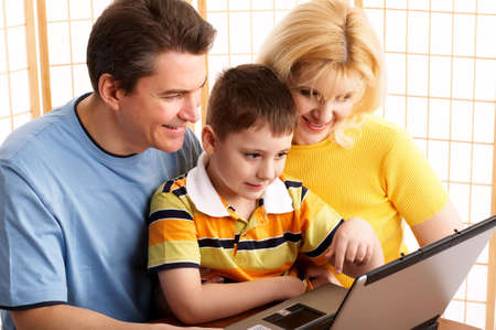 Happy family. Father, mother and boy with laptop.