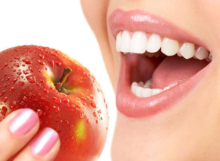 human tooth: Beautiful young woman eating a red apple. Isolated over white background  Stock Photo