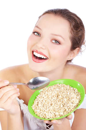 Pretty  woman holding a spoon and a plate of cereals  photo