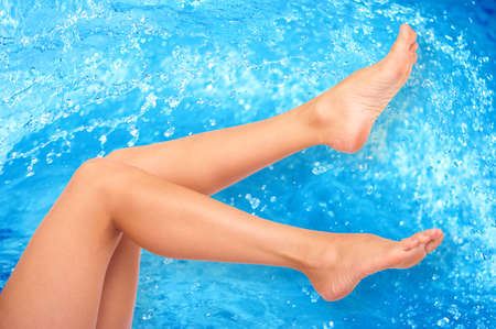 Beautiful woman legs over clean blue waterr photo