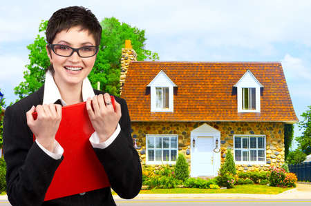 immovable: Friendly smiling real estate business woman  and a nice house.    Stock Photo