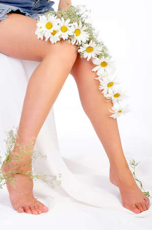 fem: Beautiful woman legs and flowers over white backgroundr Stock Photo