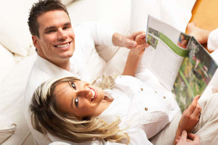 Young love couple reading magazine  in the comfortable apartment\r