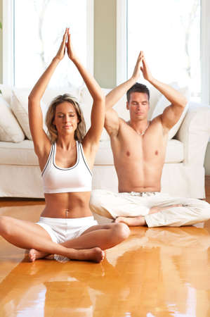 Young man and woman woman doing yoga in the sunny room  photo