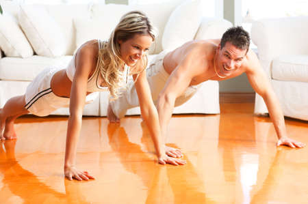 Young man and woman woman doing exercise  in the sunny roomr photo