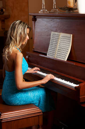 Smiling  blonde woman playing the piano 스톡 콘텐츠