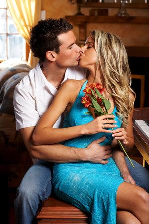 baiser amoureux: Jeune couple amoureux s'embrasser dans le cadre confortable appartement