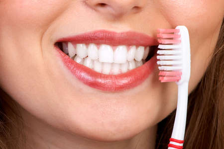 Smiling  young woman with healthy teeth holding a tooth-brush Stock Photo - 2904349