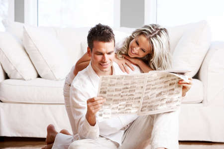 Young love couple reading magazine  in the comfortable apartmentr photo