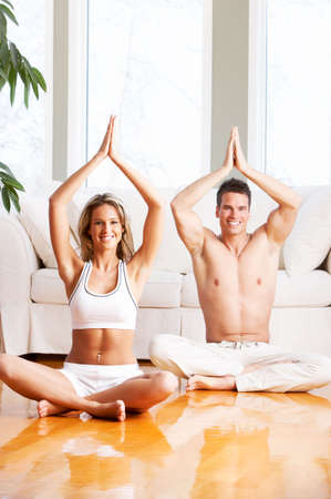 Young man and woman woman doing yoga in the sunny room Stock Photo - 2977167
