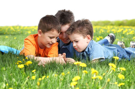 Funny smiling boys  on the green grass in the park