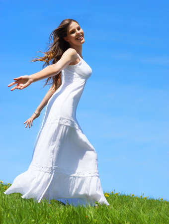 Happy young woman running  in the field