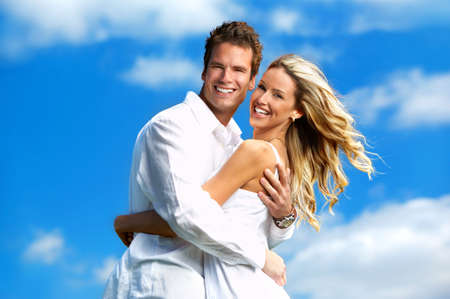 Young love couple smiling under blue skyrr photo
