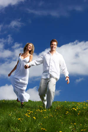 Young love couple running  under blue skyr