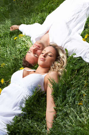 Young love couple sleeping on green grassr photo