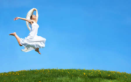 Happy young woman running  in the field  photo
