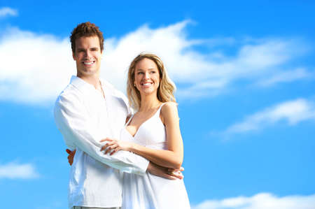 Young love couple smiling under blue skyr photo