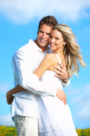 Young love couple smiling under blue skyr