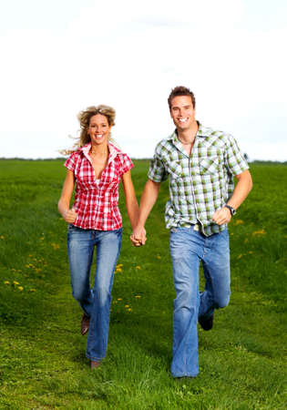 Young smiling love couple running under skyr photo