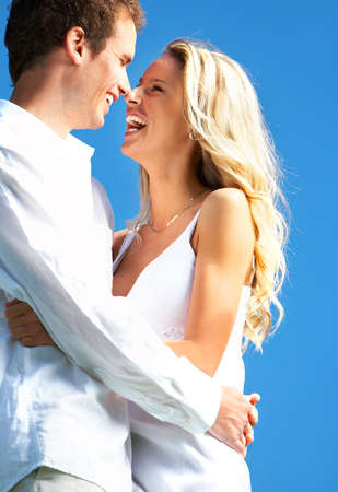 Young love couple smiling under blue sky Stock Photo - 3173404