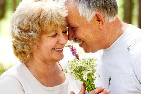 pareja abrazada: Sonriendo feliz pareja de ancianos en el amor al aire libre