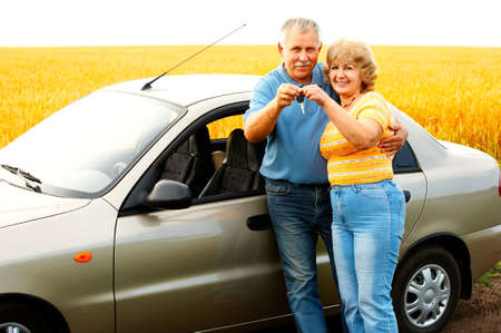 Smiling happy elderly couple  in the new car photo