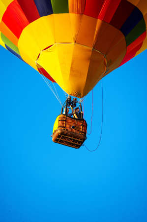 Multicoloured balloon flying in the clean blue skyr photo