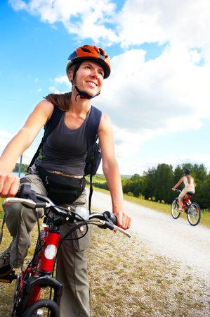 cycleway: Giovane donna sorridente in bicicletta nel parco