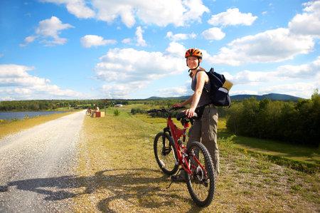 Sonriente joven mujer en bicicleta en el parque
