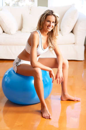 energy work: Young woman working out  in the sunny room