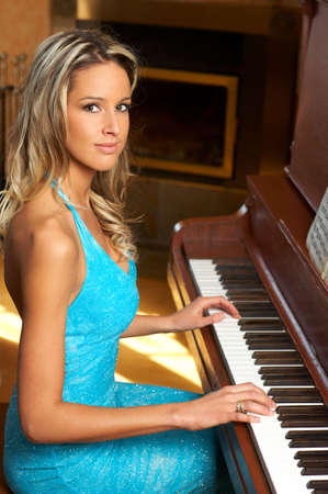 Smiling  blonde woman playing the piano\r photo