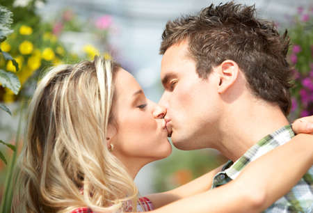 sexy couple kissing: Young love couple smiling among lots of flowers  Stock Photo
