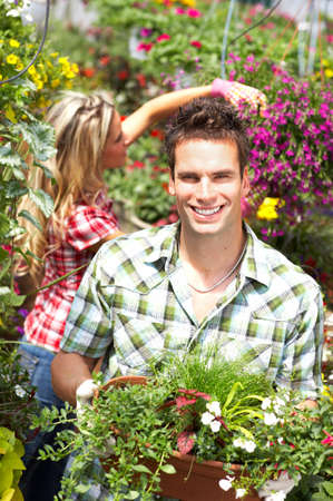 Young smiling people florists working in the gardenr photo