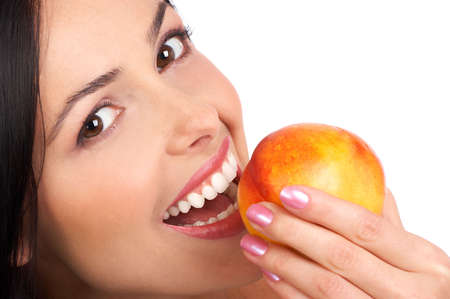 over eating: Beautiful young woman eating a peach. Isolated over white