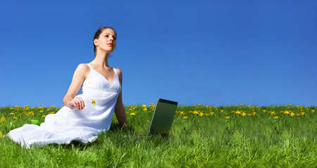 Beautiful young woman working with laptop under blue sky.   photo