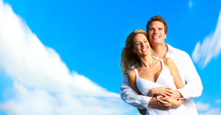 dental insurance: Young love couple smiling under blue skyrr Stock Photo