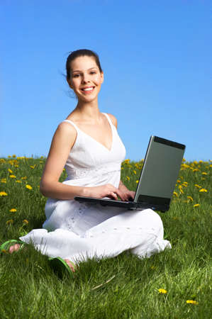 Beautiful young woman working with laptop under blue sky. Stock Photo - 3584439