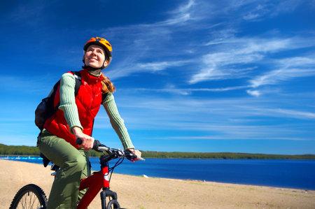 cycleway: Giovane donna sorridente in bicicletta vicino al lago  Archivio Fotografico