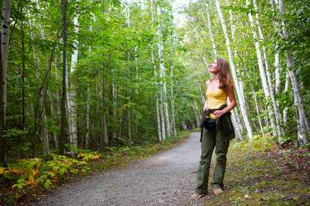 copse: Young smiling woman walking in the park
